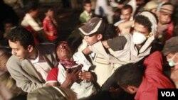 Demonstran anti-pemerintah membawa rekannya yang terluka akibat penindakan keras oleh pasukan pemerintah di Taiz (29/5).