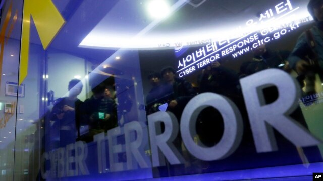 Members of media are reflected on the door of Cyber Terror Response Center as they wait to enter the lab at National Police Agency in Seoul, South Korea, March 21, 2013.