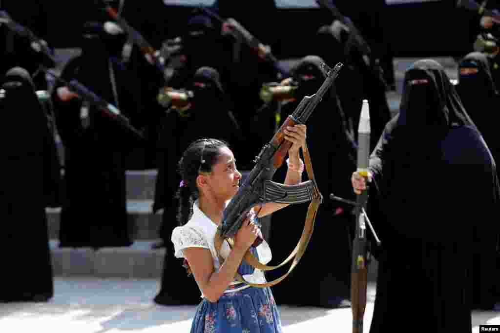 A girl holds a rifle in front of women loyal to the Houthi movement taking part in a parade to show support to the movement in Sana'a, Yemen.