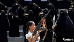 Seorang perempuan memegang senjata di depan perempuan-perempuan yang setia kepada gerakan Houthi yang ikut dalam parade dukungan di Sana'a, Yaman, 6 September 2016.