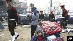 ເດັກຊາຍຄົນນຶ່ງກໍາລັງລໍຖ້າພໍ່ແມ່ ພ້ອມກັບເຄື່ອງຂອງ ຂອງລາວ ໃນຂະນະທີ່ທະຫານຍ່າງກາຍຫລັງລາວໄປ ທີ່ຈະຕຸລັດ Tahrir ທີ່ກຸງໄຄໂຣ. ວັນທີ 14 ກຸມພາ 2011.