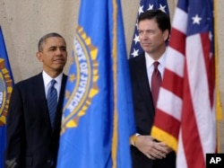 FILE - President Barack Obama stands with James Comey during the presentation of colors at Comey's installation as FBI Director, Oct. 28, 2013, at FBI Headquarters in Washington.