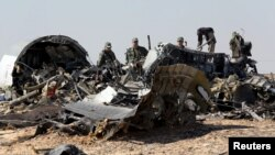 Military investigators from Russia stand near the debris of a Russian airliner at the site of its crash at the Hassana area in Arish city, north Egypt, Nov. 1, 2015.