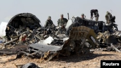 FILE - Military investigators gather Nov. 1, 2015, at the Egyptian site of a Russian airliner crash that killed all 224 people aboard. Islamic State-linked militants claimed responsibility. Now, a purported IS video threatens bloodshed in Russia.