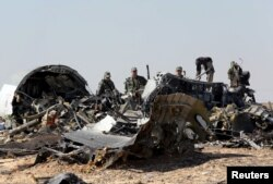 FILE - Military investigators from Russia stand near the debris of a Russian airliner at the site of its crash at the Hassana area in Arish city, north Egypt, Nov. 1, 2015.