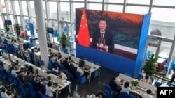 採訪博鰲論壇的記者在媒體廳觀看屏幕上顯示的中國國家主席習近平在開幕式上講話的視頻。 (2021年4月20日)
