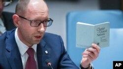 Perdana Menteri sementara Ukraina Arseniy Yatsenyuk berbicara di Dewan Keamanan PBB di New York sambil memegang buku perjanjian PBB (13/3). (AP/John Minchillo)