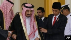 Indonesian President Joko Widodo (R) assists Saudi King Salman (C) as they walk during their meeting at the presidential palace in Bogor, West Java, Indonesia, March 1, 2017.