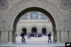 FILE - Students walk on campus at Stanford University in Stanford, Calif., Jan. 13, 2016.