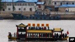 Sebuah perahu wisata China melewati kapal patroli Korea Utara yang sedang berlabuh di tepi sungai Sinuju, Korea Utara, terlihat dari kota perbatasan Dandong di propinsi Liaoning, China (Foto: dok).