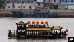 북한 신의주 강변의 중국인 관광보트 옆으로 북한 순찰선이 지나가고 있다. (자료사진)