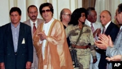 Libyan leader Muammar Gaddafi (C) arrives at Cairo university for a meeting with university professors, The armed woman to the right of Gaddafi is his personal bodyguard, May 27, 1996.