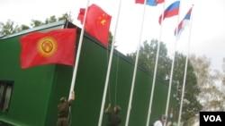 中亞國家經常與中國和俄羅斯共同參加一些活動。2014年在莫斯科郊外的軍事比賽活動中,俄羅斯軍人升中國和吉爾吉斯國旗。(美國之音白樺拍攝)