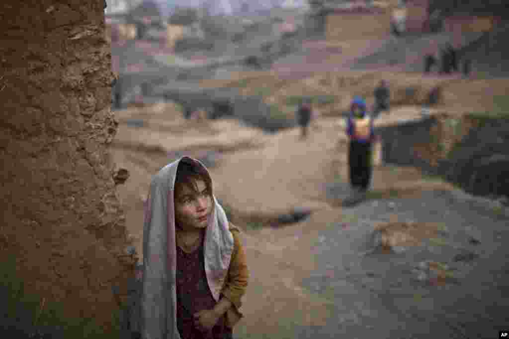 Afghan refugee Sayma Naseeb, 4, stands by the doorway of her family's mud house in a poor neighborhood on the outskirts of Islamabad, Pakistan.
