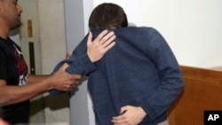 FILE - A 19-year-old dual U.S.-Israeli citizen covers his face as he is brought to court in Rishon Lezion, Israel, March 23, 2017. Israeli police said they have arrested a Jewish Israeli man who is the prime suspect behind a wave of bomb threats against Jewish community centers and other institutions in the United States.