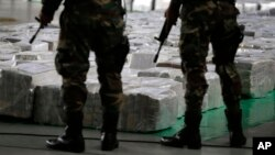 FILE - Police officers stand guard over seized cocaine.