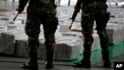 FILE - Police officers stand guard over seized cocaine they present to the press in Lima, Peru, Sept. 1, 2014.