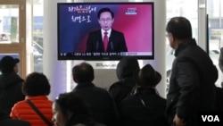 Warga Seoul menyimak pidato Tahun Baru dari Presiden Lee Myung-bak di sebuah stasiun kereta di Seoul, Korea Selatan (2/1).