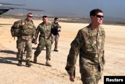 U.S. Army General Jospeh Votel, right, head of Central Command, visits an airbase at an undisclosed location in northeast Syria, Feb. 18, 2019.