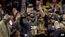 LeBron James dari Cleveland Cavaliers (tengah) merayakan kemenangan dalam final NBA melawan Golden State Warriors di Oakland, California (19/6). (AP/Eric Risberg)