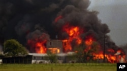 FILE - Fire engulfs the Branch Davidian compound near Waco, Texas on Monday, April 19, 1993.