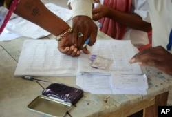 An Indian polling official helps a woman put her thumb imprint before proceeding to cast her vote at a polling station at Samastipur district, in India's eastern state Bihar, October 12, 2015.
