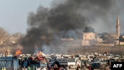 Asap mengepul dari kubu pertahanan terakhir ISIS di kawasan Baghuz, provinsi Deir el-Zour, Suriah (9/3).