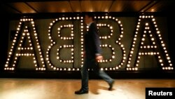 "FILE - A man walks past the lit logo of the legendary Swedish pop group ABBA at ""ABBA — The Museum"" in Stockholm, May 6, 2013."
