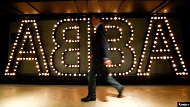 "A man walks past the lit logo of the legendary Swedish pop group ABBA at the new ""ABBA - The Museum"" in Stockholm, May 6, 2013."