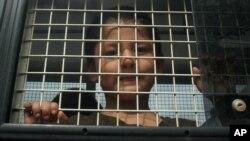 2014年3月15日一名維吾爾族男孩站在泰國宋卡府南部一輛警車內。他是人口販運營地被營救出的200人中的一個。