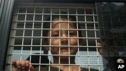 تھالی لینڈ میں پولیس کی گاڑی میں یغور نسل کا ایک مسلمان سوار ہے جسے حکام نے 200 افراد کے ایک گروپ کے ساتھ غیرقانونی طور پر سرحد عبور کرنے کے جرم میں پکڑا۔ فائل فوٹو