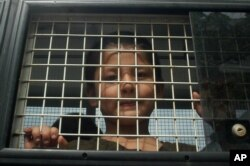 FILE - Ethnic Uighur Muslim boy stands inside a police van in Khlong Hoi Khong of southern Songkhla province, Thailand, March 15, 2014. He was in a group of 200 people rescued from a human trafficking camp.