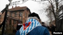 """ພວກທີ່ລອດຊີວິດມາໄດ້ ແລະເພື່ອນ ພາກັນຍ່າງຜ່ານປ້າຍທີ່ ຂຽນວ່າ """"Arbeit Macht Frei"""" ທີ່ມີຄວາມໝາຍວ່າ ວຽກງານ ແມ່ນເຮັດໃຫ້ທ່ານເປັນອິດສະຫຼະ (""""Work Sets You Free"""") ໃນຮົ້ວຂອງສູນມໍລະນະຂອງນາຊີ ເຢຍຣະມັນ ຢູ່ Auschwitz, ໃນວັນຄົບຮອບ 73 ປີ ທີ່ຖືກປົດປ່ອຍ ແລະວັນລະລຶກເຖິງ ພວກທີ່ລອດຊີວິດມາໄດ້ ຈາກໂຮໂລຄອສ, ໃນນະຄອນຄອສວີຊິມ, ໂປແບນ, 27 ມັງກອນ 2018."""