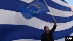 A man waves an European flag in front of giant Greek one, during a pro-European demonstration in front of the Greek parliament in Athens on June 22, 2015.