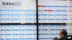 Dua orang warga tengah mengamati papan elektronik di sebuah perusahaan sekuritas Tokyo (21/9).
