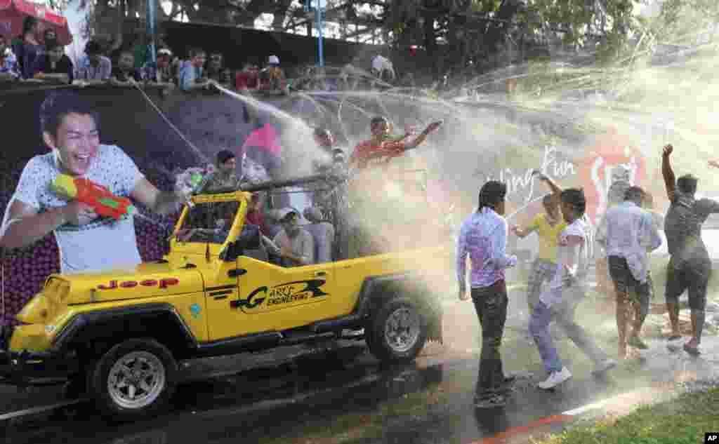 Revelers on a vehicle are sprayed with water during the traditional Thingyan celebrations in Rangoon, Burma. Burma celebrated its annual water festival, known as Thingyan, marking the start of the New Year according to the traditional Buddhist calendar.