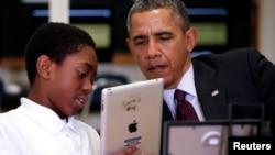 El presidente Barack Obama ve una habla con un estudiante mientras ve su iPad proporcionada por la escuela.