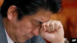 Perdana Menteri Shinzo Abe bereaksi dalam sesi di majelis tinggi Parlemen Jepang di Tokyo (28/1). (AP/Shizuo Kambayashi)