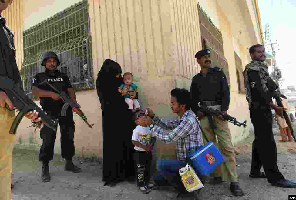Pakistani policeman stand guard as a health worker administers polio drops to a child during a polio vaccination campaign after a day after gunmen staged an attack in Karachi.