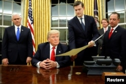 FILE - White House Staff Secretary Rob Porter gives U.S. President Donald Trump, flanked by Vice President Mike Pence, left, and Chief of Staff Reince Priebus, right, the document to confirm Secretary of Defense James Mattis.