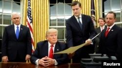 罗伯·波特将批准任命马蒂斯为国防部长的文件交给川普总统签署。在他们身边的是彭斯副总统和时任白宫办公厅主任的普里伯斯。(2017年1月20日)