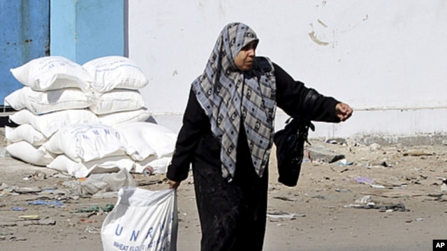 A Palestinian woman drags a sack of flour received as food supplies at a United Nations food aid distribution center, Shati refugee camp, Gaza City. (file photo)