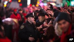 A New York police officer helps manage the crowd during the hours leading up to the annual New Year's Eve celebration in Times Square, Dec. 31, 2015, in New York.