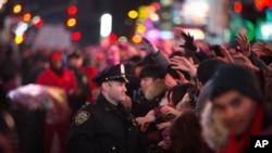지난 31일 밤 새해 맞이 행사가 열린 뉴욕 타임스퀘어 광장에서 한 경찰(가운데)이 인파를 통제하고 있다.