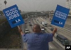 Christian Del Cid, du sud de Los Angeles, agite des pancartes réclamant du travail de qualité (22 septembre 2011)
