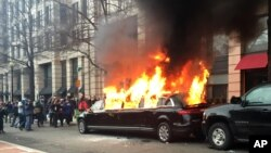 FILE - Protesters set a parked limousine on fire in downtown Washington during the inauguration of President Donald Trump, Jan. 20, 2017.