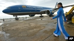 FILE - A Vietnam Airlines employee walks out to greet a newly delivered Boeing 777-200ER at Noi Bai airport in Hanoi, Vietnam on Sunday Sept. 19, 2004. (AP Photo/Richard Vogel)