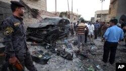 ກໍາລັງຮັກສາຄວາມສະຫງົບ ກວດກາເບິ່ງ ສະຖານທີ່ມີການໂຈມຕີ ດ້ວຍລະເບີດລົດທີ່ເມືອງ Basra, ທີ່ຢຸ່ຫ່າງຈາກນະຄອນ Baghdad 550 ກິໂລແມັດ ໄປທາງທິດໃຕ້ ໃນວັນທີ 14 ກໍລະກົດ 2013.