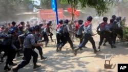 Polisi Myanmar dengan senjata pentungan mengejar para pemrotes di Letpadan, 140 kilometer sebelah utara Rangoon, Selasa (10/3).