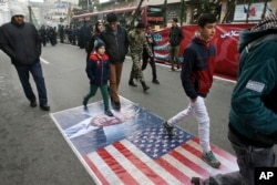 Iranians march on a portrait of U.S. President Donald Trump and the picture of U.S. flag in an annual rally commemorating the anniversary of the 1979 Islamic revolution, which toppled the late pro-U.S. Shah, Mohammad Reza Pahlavi, in Tehran, Iran, Feb. 10
